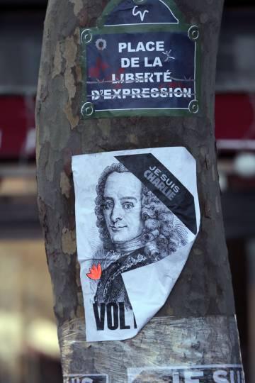 """Un cartel en el que se lee """"Plaza de la Libertad de Expresión"""" y una imagen de Voltaire, en un árbol en la plaza de la República de París, en 2015."""