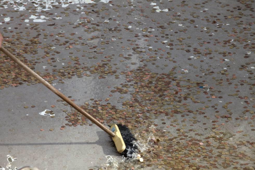 Un empleado del Ayuntamiento de Roma recoge algunas de las monedas arrojadas a la Fontana di Trevi, el 2 de mayo de 2011.
