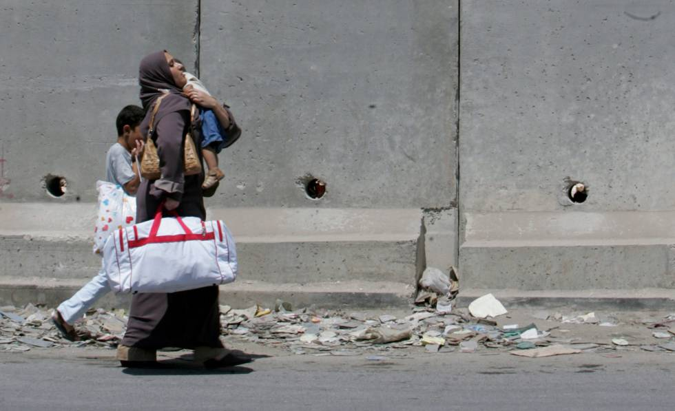 Una palestina y sus hijos caminan por la localidad de Aram.