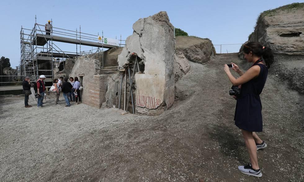 Una visitante fotografía una inscripción en la 'Regio V' de Pompeya.
