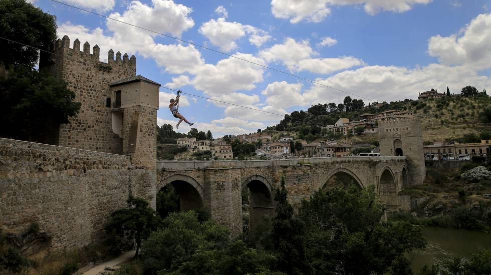 Una chica se tira con una tirolina por encima del río Tajo en Toledo.