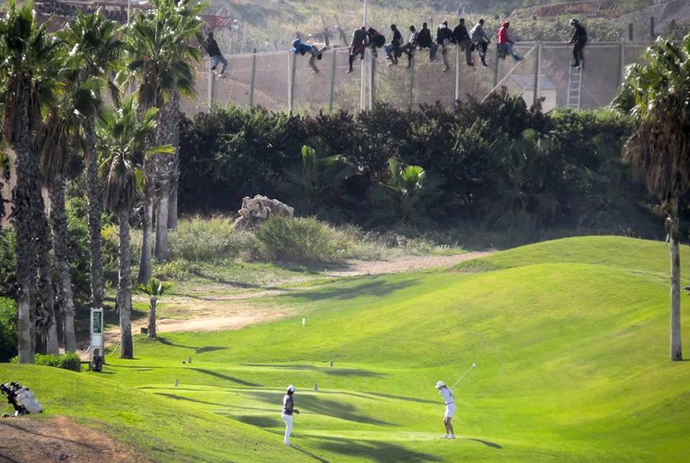 Al menos 12 inmigrantes, encaramados en la valla de Melilla frente al campo de golf situado al lado de la alambrada que separa la ciudad autonoma de Marruecos.