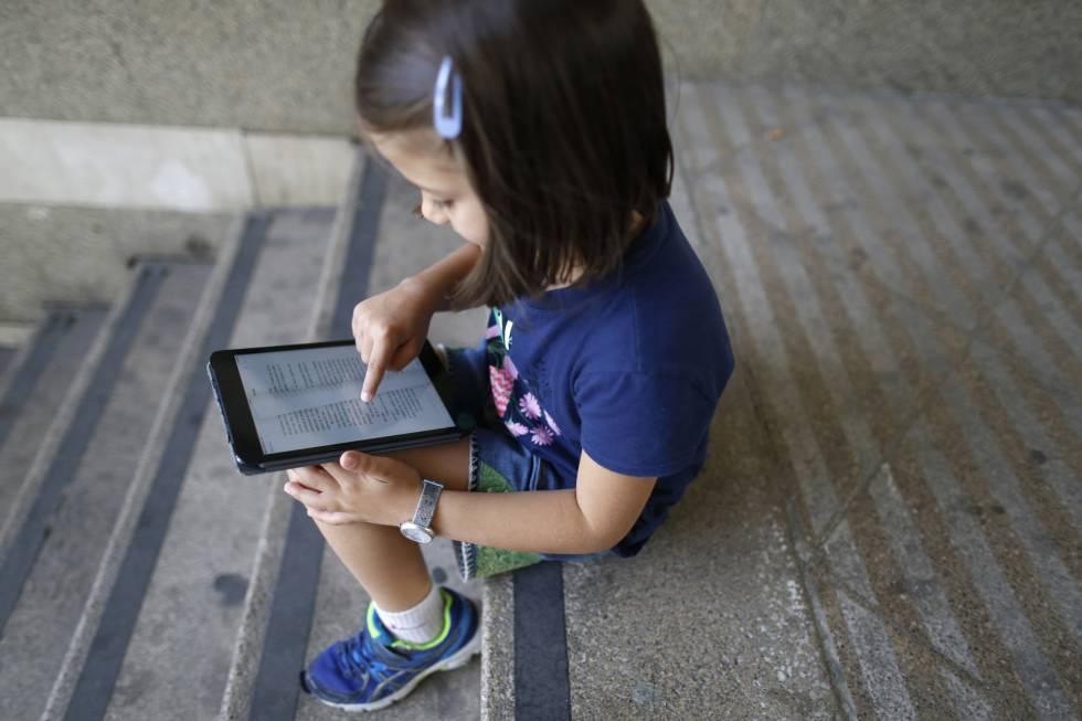Una niña lee un libro en una tableta.