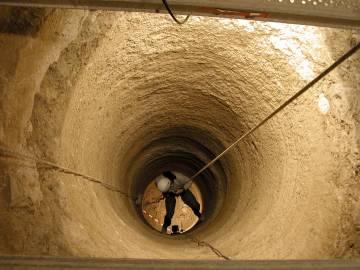 Un arqueólogo desciende por el pozo del dolmen de Menga.