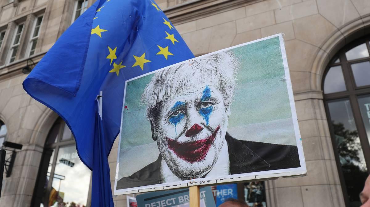 Pancarta en una manifestación en Londres frente al Parlamento británico, con Boris Johnson caricaturizado como el Joker. rn