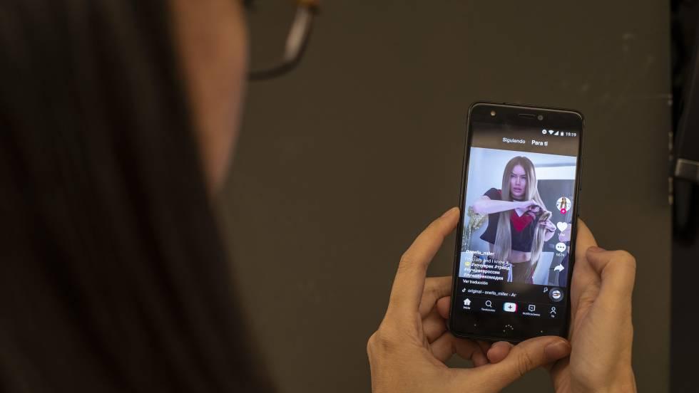 Uma mulher assiste a um vídeo no TikTok. No vídeo, o trailer do app.
