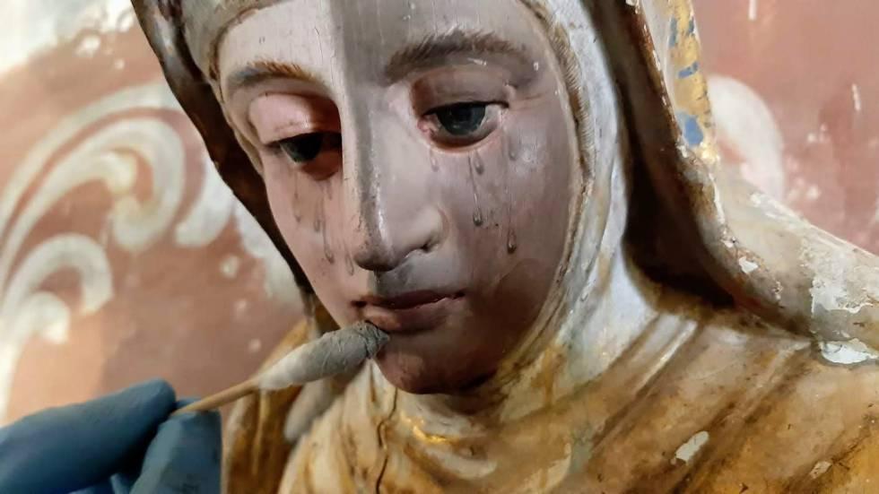 Proceso de limpieza de la Virgen, en la parte alta del retablo de Quintanilla de Riofresno.