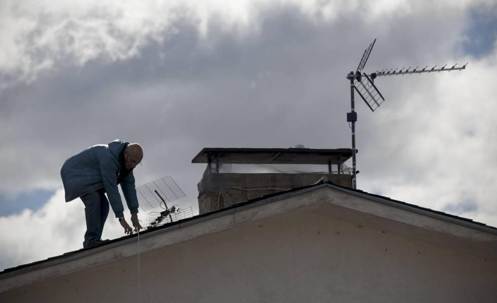 Un antenista cambia una antena antigua y resintoniza una nueva en una vivienda de Madrid.