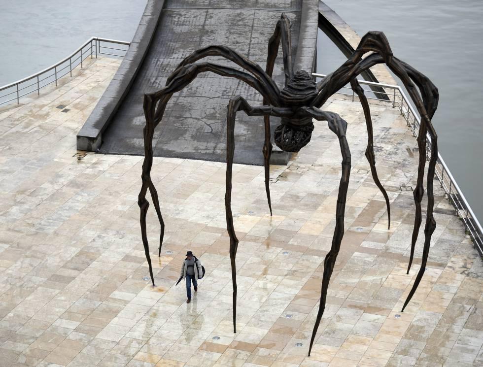 Una persona camina bajo la escultura de Louise Bourgeois 'Mamá', en las inmediaciones del Museo Guggenheim de Bilbao, el 27 de abril.
