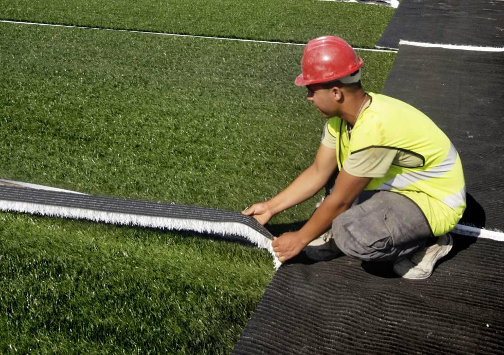 un operario instala csped artificial en un campo de barcelona