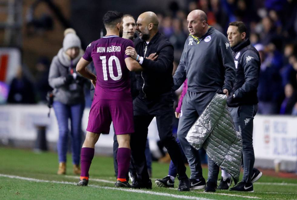 Guardiola sujeta a Agüero ante el entrenador del Wigan Athletic, Paul Cook.