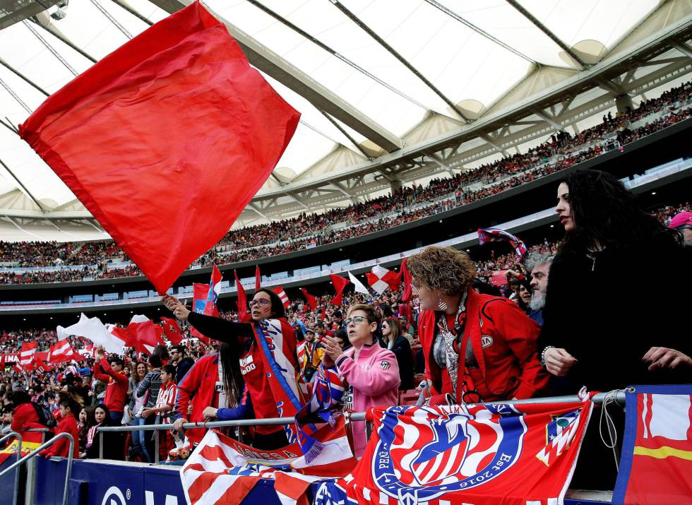 Torcedoras do Atlético de Madrid exibem bandeiras alvirrubras nas arquibancadas.