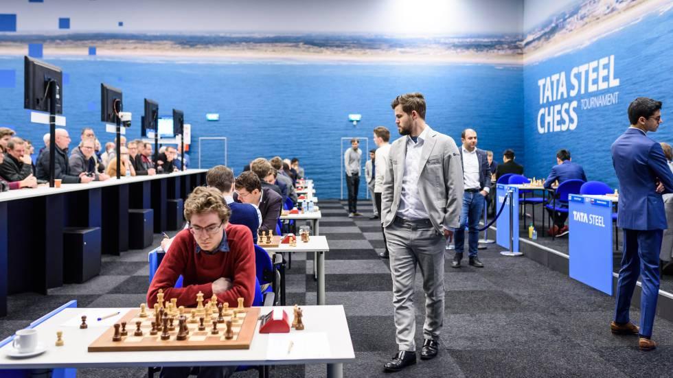 Magnus Carlsen pasea por la sala de juego en Wijk aan Zee durante su partida de este lunes; en primer plano, el español David Antón, participante en el Torneo B