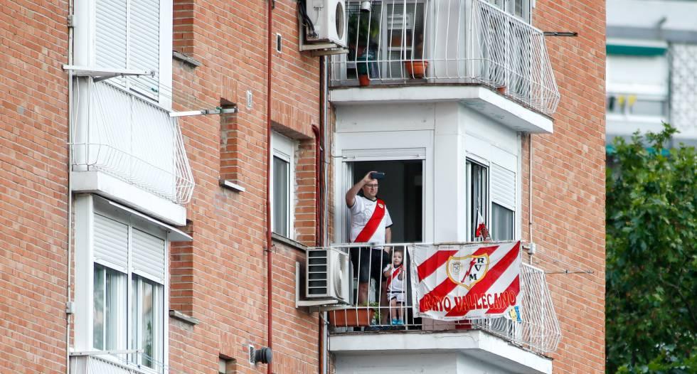 Un aficionado del Rayo Vallecano mira un partido en Vallecas desde su balcón.