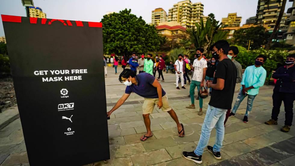 Los ciudadanos indios acuden al dispensador de máscaras que LaLiga ha instalado en Bombay.