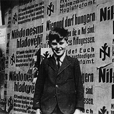 Petr Ginz, en 1940, ante un muro con carteles del Reich invitando a los judios de Praga a registrarse.