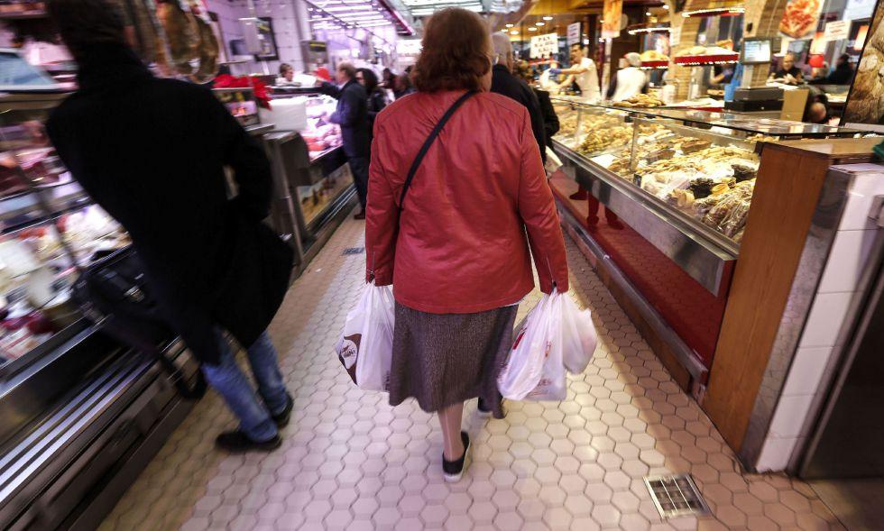 Una mujer acarrea con varias bolsas en el Mercado Central de Valencia
