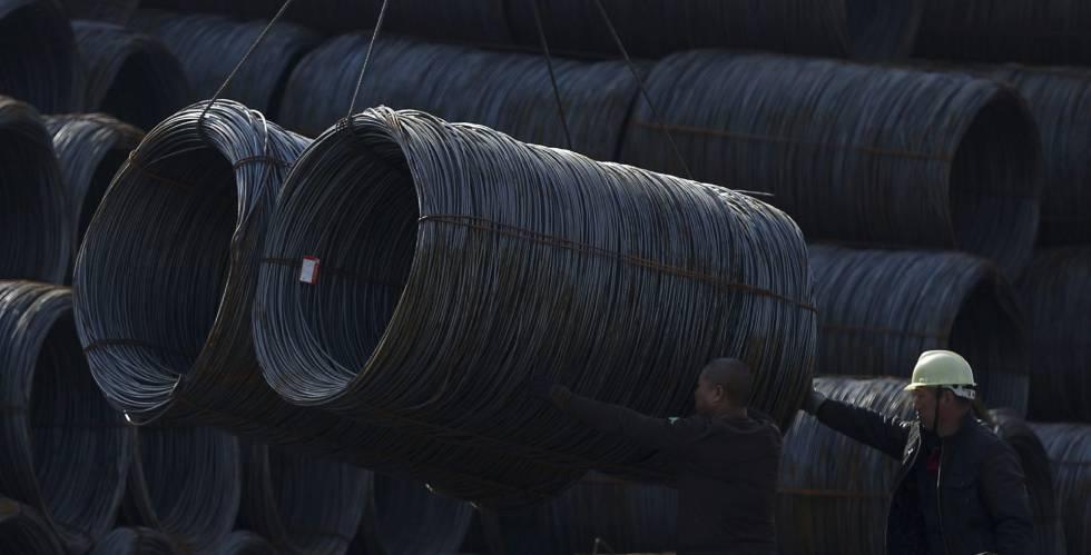 Dos obreros trabajan en una fábrica de acero en Shenyang, noreste de China.