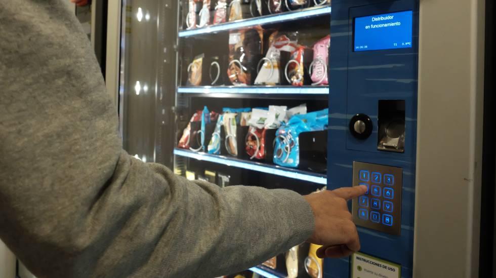 Un hombre compra productos en una máquina expendedora.