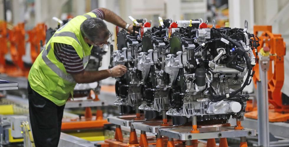 Un empleado de Ford trabaja con un motor diésel en una planta de Londres.