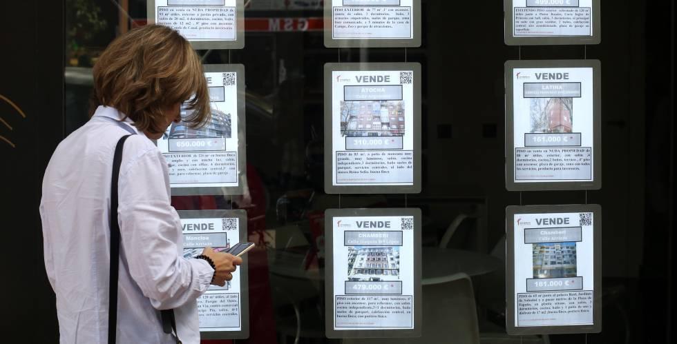 36ea95dacd528 Una mujer apunta en su teléfono móvil frente a una inmobiliaria en Madrid.