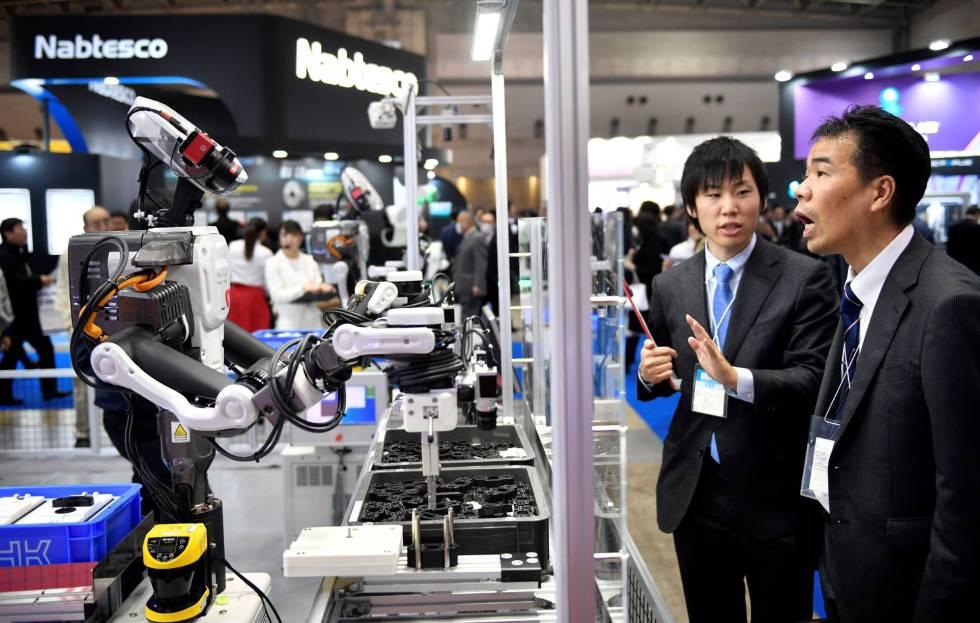 Un par de asistentes observan un robot industrial en una feria de robótica en Tokio.