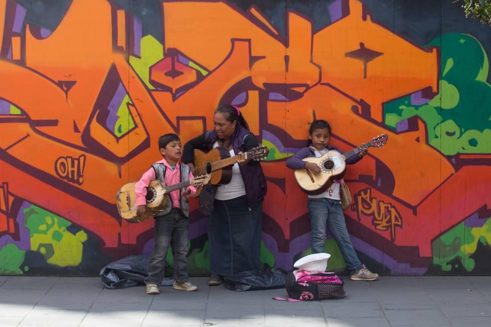 Una señora con dos menores de edad cantan en las calles de la Ciudad de México.
