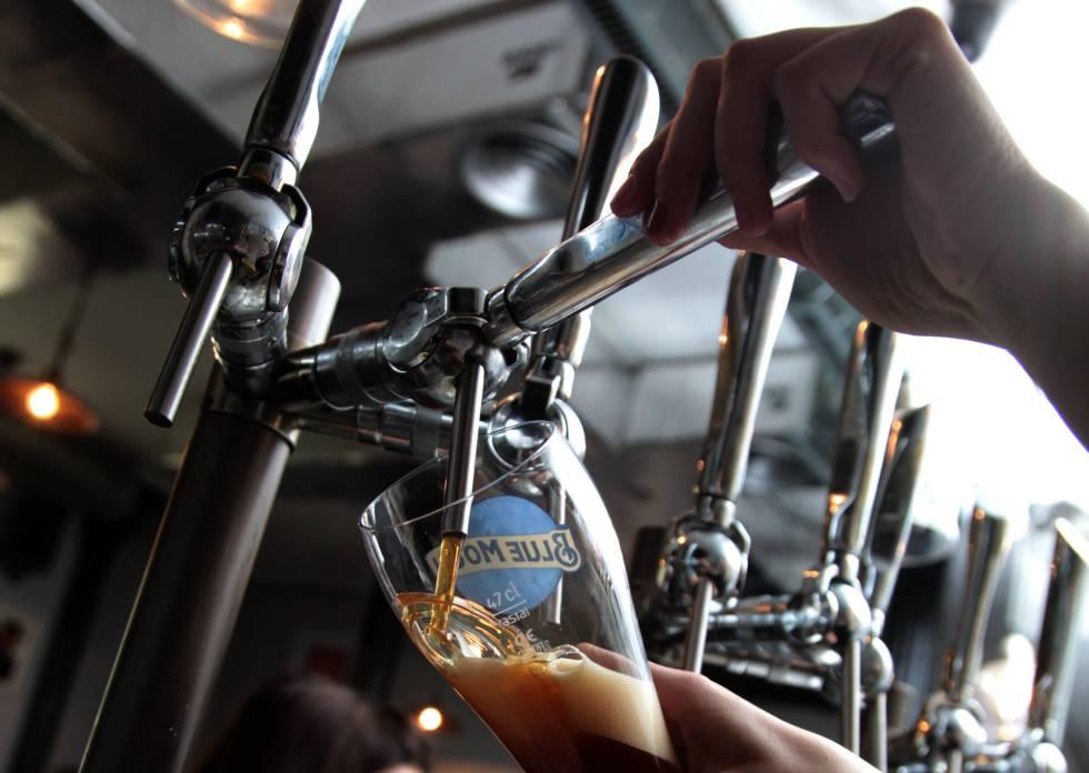 Una camarera sirve una cerveza en un bar de Madrid.
