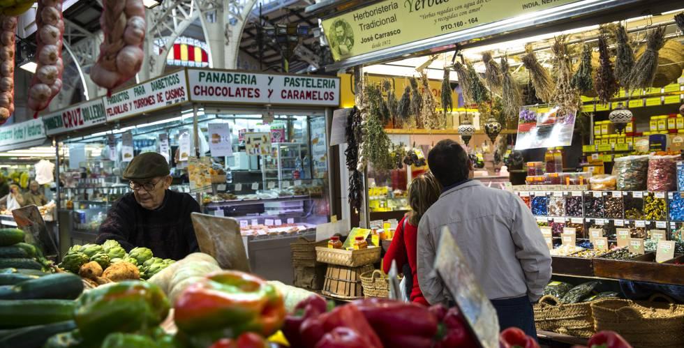 Puesto de frutas y verduras y una panadería, en el Mercado Central de Valencia.