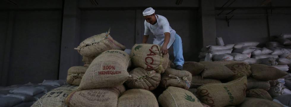Un operario mueve sacos de cacao en una fábrica en México.