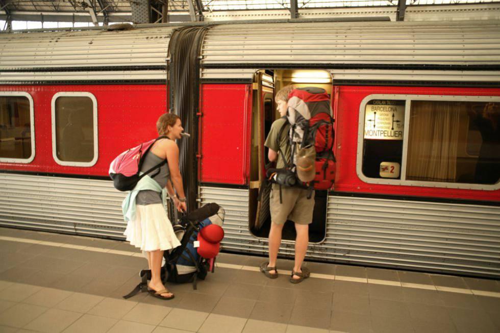 Dos jóvenes mochileros viajan en tren por Europa.