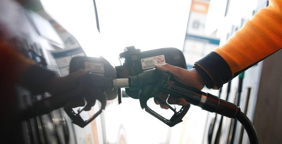 El empleado de una gasolinera echa diésel en un automóvil.