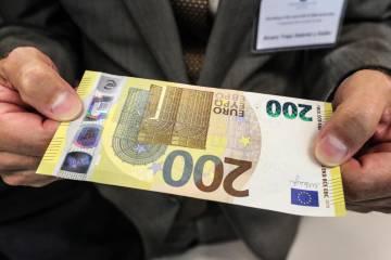 Un periodista sostiene el nuevo billete de 200 euros en la sede del BCE este lunes.