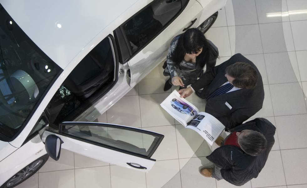 Un vendedor atiende a una pareja en un concesionario de coches en Madrid.