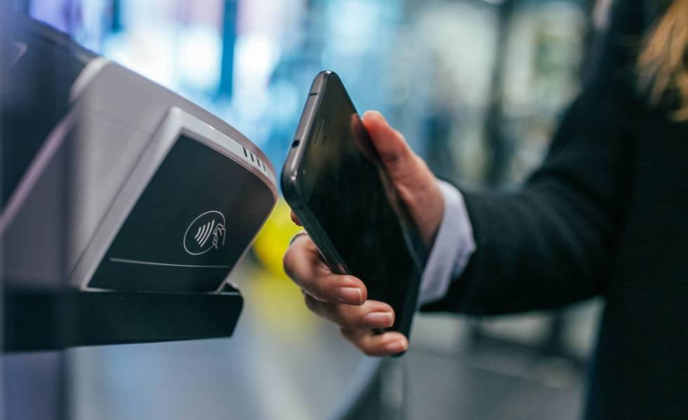 Una usuaria paga una compra con su móvil.