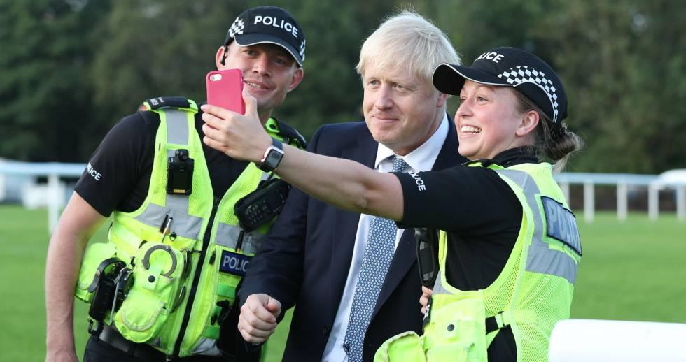 El primer ministro británico, Boris Johnson se fotografía con dos policías en un acto el pasado viernes.