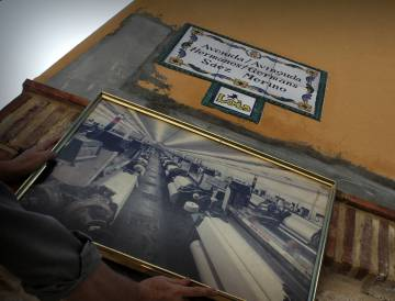 Placa de la avenida dedicada a los creadores de Lois en Millares y, debajo, foto de cómo era la antigua fábrica.