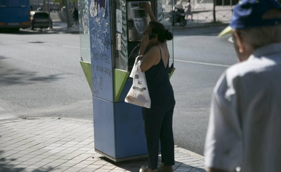 Una mujer usa una cabina telefónica en Madrid.