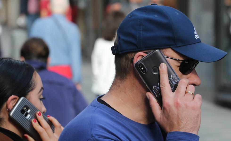 Dos personas hablan por el móvil en el centro de Madrid.
