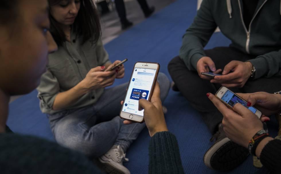 Jóvenes viendo redes sociales en su teléfono móvil.