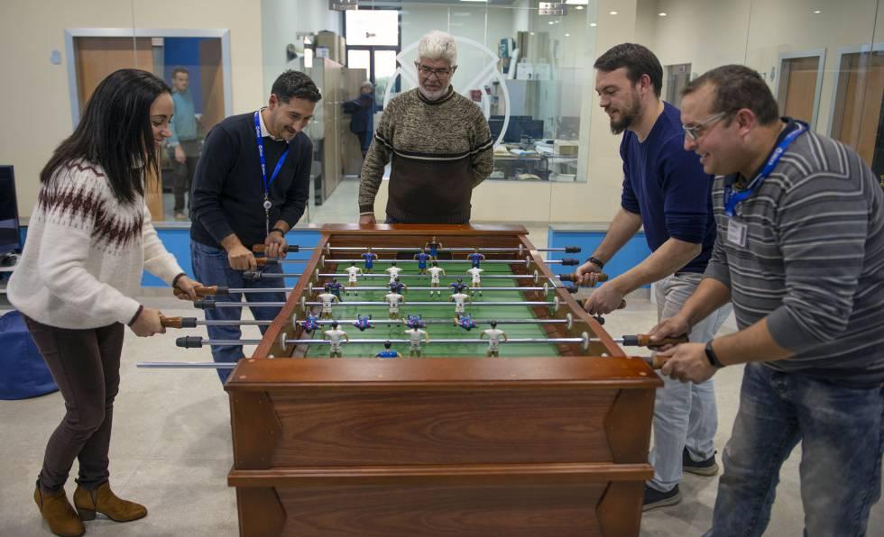 Unos empleados juegan al futbolín en una sala de ocio de la empresa.