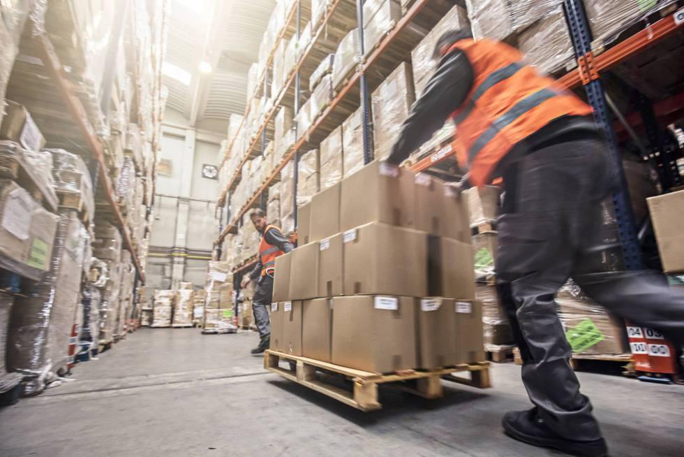 Unos trabajadores trabajan en la organización de un alamacen logístico.