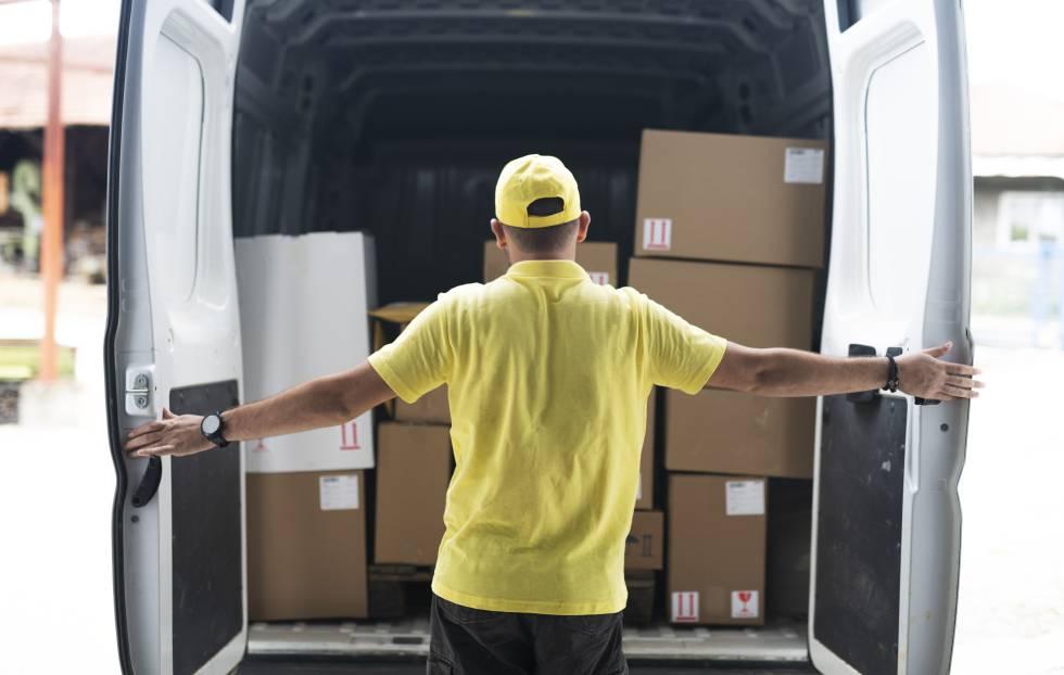Un repartidor cierra las puertas de su furgoneta tras haberla cargado hasta la mitad.