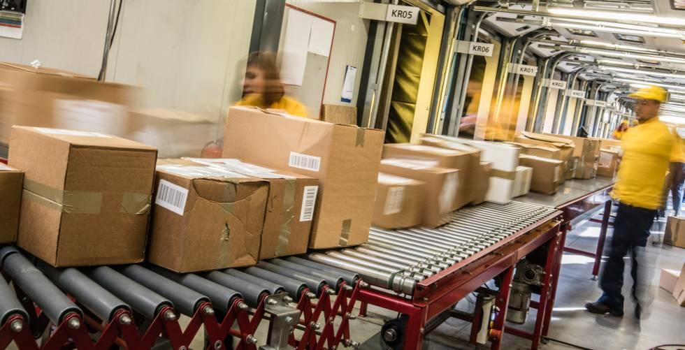 Varios trabajadores de un centro logístico organizan miles de paquetes durante una jornada laboral.