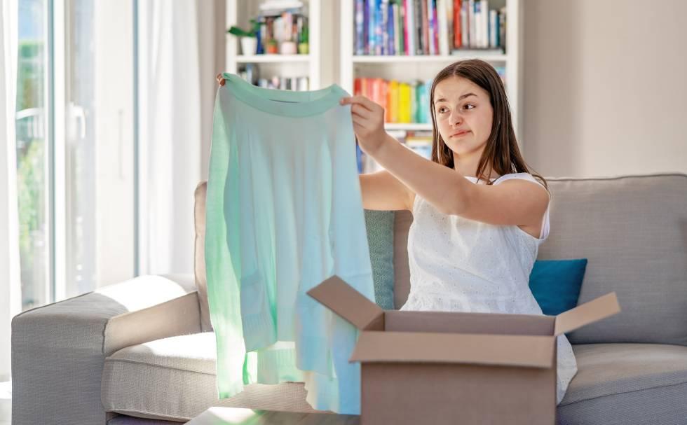 Una chica comprueba que ha comprado por Internet una blusa con una talla equivocada.