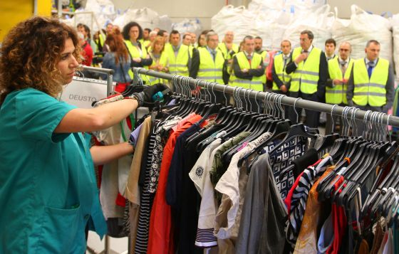 An employee of the new recycling plant in Mungia, in the Basque Country, sorts through clothes for recycling.