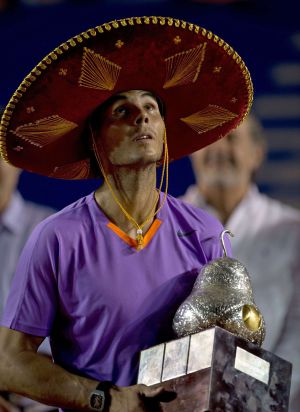 Rafael Nadal of Spain wears a traditional Mexican mariachi hat while holding the winning trophy in Acapulco.