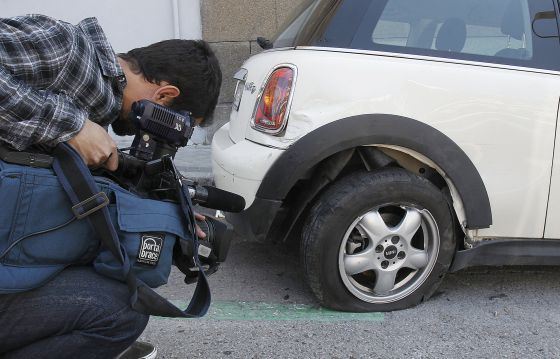 A news camera gets a shot of some of the damage done by the car of Miguel Ángel Rodríguez.
