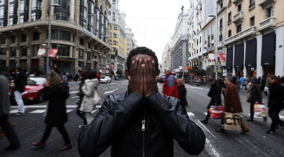 Yafar shields his face on a Madrid street.