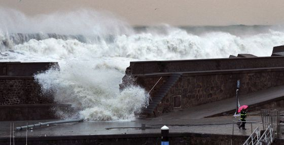 A man looks as a wave breaks through a seawall in Bermeo, Vizcaya province, on Sunday.
